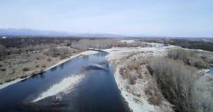 Het bewegen zich vooruit over rivierbed in de herfst of de winter Openlucht zonnig aard scape rivierbed dichtbij bos wilde antenn stock video