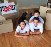 Het bewegende huis van de familie op vloer die bij de camera glimlacht Stock Foto