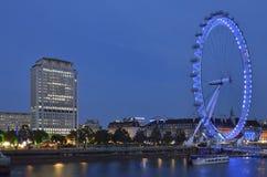 Het bewegende/roterende Oog van Londen in de nacht met omgeving Stock Afbeelding