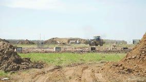 Het bewegende zand van de bulldozermachine op bouwwerf De apparatuur van de bouw Het bewegende zand van de kruippakjebulldozer stock videobeelden