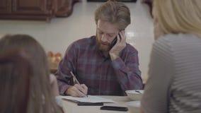 Het bezige vader spreken door celtelefoon, heeft hij geen tijd en besteedt geen aandacht aan zijn dochter en vrouw De familie van stock video