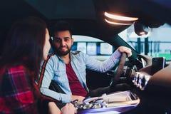 Het bezoekende autohandel drijven Het mooie paar spreekt en glimlacht terwijl het zitten in hun nieuwe auto E stock fotografie