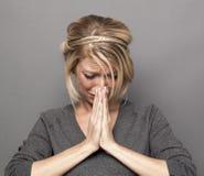Het bidden concept voor diepbedroefde jonge blonde vrouw stock foto's