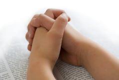 Het bidden handen op bijbel stock fotografie