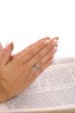Het bidden handen op bijbel Stock Foto's