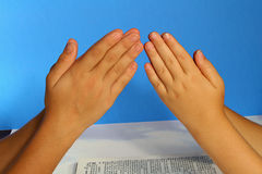 Het bidden handen op blauw royalty-vrije stock afbeeldingen