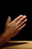 Het bidden handen op donkere achtergrond Royalty-vrije Stock Foto