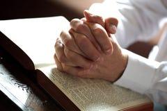 Het bidden handen op een open bijbel stock afbeeldingen