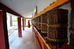 Het bidden wiel in boeddhistische tempel met een monnik op achtergrond stock fotografie