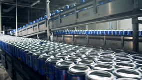 Het bier in blikken die zich op een transportband bij een brouwerij bewegen, sluit omhoog stock footage