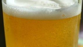 Het bier wordt gegoten in een glas Mooie bellenvlieg in een glas schuimend bier stock footage