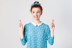 Het bijgelovige tienermeisje met gemberhaar en mooi gezicht die vingers voor goed geluk kruisen, die haar wensen waar, hav komen  stock afbeelding