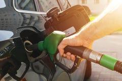 Het bijtanken van de auto bij een pomp van de benzinestationbrandstof De hand opnieuw vullende en pompende benzineolie van de men stock foto