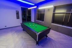 Het Biljartruimte van de snookerpool, groene lijst met volledige reeks ballen in een moderne ruimte met neonlichten stock afbeelding