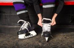 Het Binden van het kind de Vleten van het Hockey in Kleedkamer stock foto