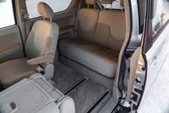 Het binnenland van de auto in de rug van minivan met een brede open automatische deur en een mening van de voor en achterzetels i royalty-vrije stock afbeelding