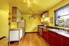 Het binnenland van de keukenruimte met gele muren en rode kabinetten Royalty-vrije Stock Foto's