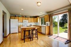 Het binnenland van de keukenruimte met lichtbruin kabinetten en eiland Stock Foto's