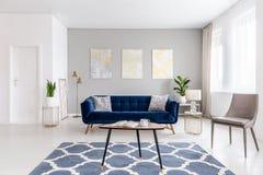 Het binnenland van de open plekwoonkamer met modern binnen meubilair van een marineblauwe sofa, een beige leunstoel, een koffieta stock foto