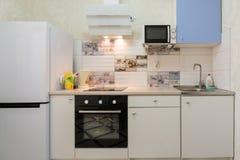 Het binnenland van een compacte keuken in flatgebouw stock afbeelding