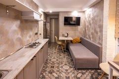 Het binnenland van een kleine woonkamer in de hotelruimte, dat met keuken wordt gecombineerd royalty-vrije stock afbeeldingen