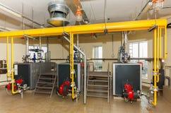 Het binnenland van industrieel gasketelhuis met vele pijpen en kookt Stock Foto