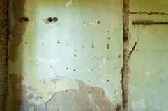 Het binnenlandse pleister van de huismuur met kogelgaten en schade van granaatscherf van granaat Royalty-vrije Stock Afbeelding