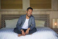 Het binnenlandse portret van de jaren '30 gelukkige en knappe mens thuis in toevallige overhemd en jeans die op bed zitten ontspa royalty-vrije stock foto