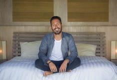 Het binnenlandse portret van de jaren '30 gelukkige en knappe mens thuis in toevallige overhemd en jeans die op bed zitten ontspa stock afbeelding