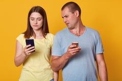 Het binnenschot van jonge marrieds met mobiele telefoons, toont geposte foto's in sociale netwerken aan, doorbladert in Internet  royalty-vrije stock foto's