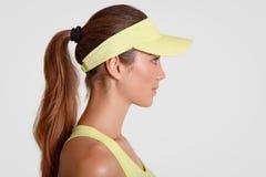 Het binnenschot van nadenkende tennisspeler bevindt zich zijdelings, draagt sportsclothes, heeft poneystaart, stelt tegen witte a royalty-vrije stock afbeeldingen