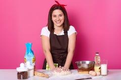 Het binnenschot van positieve huisvrouw kneedt deeg, bakt heerlijk iets, omringd met eieren, glas melk, olie, deegrol, stock afbeelding