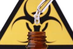 Het bio gevaar pipet daling en fles Stock Fotografie