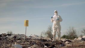 Het biologische gevaar, hazmat mens in beschermende kleding toont teken sparen de planeet op vuilnisstortplaats met wijzer stock videobeelden