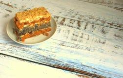 Het biscuitgebak met papaverzaden op een plaat ligt op een houten lijst stock afbeelding