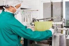 Het Blad van chef-kokpreparing green pasta in Machine Stock Fotografie