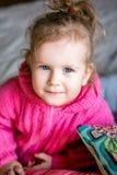 Het blauw-eyed leuke meisje in een roze jasje onderzoekt de camera royalty-vrije stock foto's