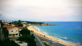 Het blauw-turkooise overzees wordt gewassen door een zandig strand op een de zomerdag op de kust van Tarragona royalty-vrije stock foto's