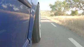 Het blauwe auto drijven op een bergweg met witte wielen stock videobeelden