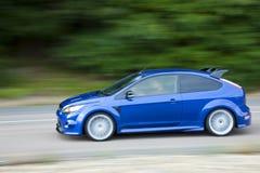 Het blauwe auto drijven snel bij de landweg Stock Afbeelding