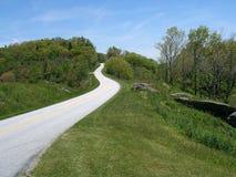 Het blauwe Brede rijweg met mooi aangelegd landschap van de Rand stock afbeelding