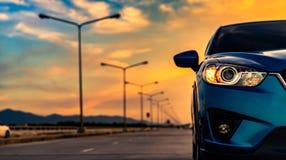 Het blauwe compacte SUV-licht van de auto open die koplamp op betonweg dichtbij de berg bij zonsondergang met mooie hemel en wolk stock foto's