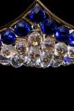 Het blauwe die close-up van de kristalkroonluchter met kettingen op zwarte achtergrond wordt geïsoleerd Stock Afbeeldingen