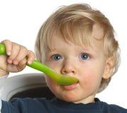 Het blauwe eyed babyjongen proberen eet Stock Afbeelding