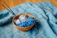 Het blauwe garen in weinig mand met naalden en haakt Royalty-vrije Stock Foto