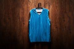 Het blauwe hangen van basketbaljersey op een houten muur Stock Fotografie