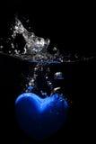 Het blauwe hart bespatten op water Stock Afbeeldingen