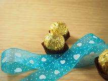 Het blauwe hemellint met hartvorm, chocoladeballen, behandelde gouden aluminium Stock Afbeeldingen
