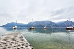 Het blauwe landschap van het watermeer met laarzen en groene boom bij regenachtige dag Traunsee, Gmunden, Oostenrijk neutrale kle royalty-vrije stock fotografie