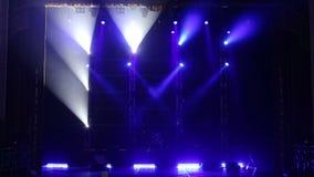 Het blauwe licht opvlammen en witte stralen op een leeg stadium in dark stock video